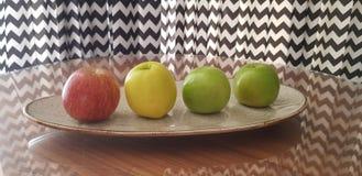 Un plato con cuatro manzanas de diversos colores fotografía de archivo libre de regalías