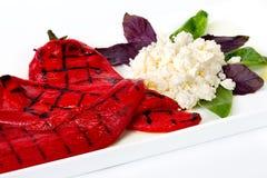 Un plato de la pimienta roja y del queso asados a la parilla Imagen de archivo libre de regalías