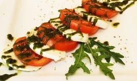 Un plato del tomate y el brynza con pesto sauce fotografía de archivo