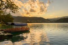 Un pletna, un barco tradicional de Eslovenia, en el lago sangrado con la iglesia y la luz evning en el fondo imagen de archivo libre de regalías