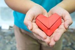 Un pli de papier rouge comme forme de coeur chez la main de la femme Une femme tenant le coeur d'origami avec la main deux r Photo stock