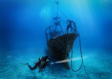 Un plongeur autonome féminin explore un naufrage submergé image libre de droits