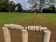 Un plus ?troit des tron?ons et des cautions de cricket sur une bande boueuse photo stock