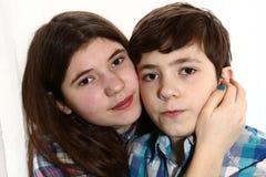Un plus jeune brothe d'enfants de mêmes parents de l'adolescence et une soeur plus âgée étreignent Photographie stock