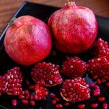 Un poco de fruta roja jugosa madura de la granada en la placa Gran del Punica Imagenes de archivo