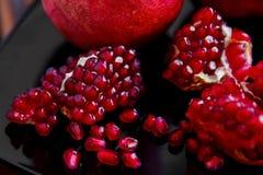 Un poco de fruta roja jugosa madura de la granada en la placa Gran del Punica Fotos de archivo libres de regalías