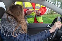 Un polic?a civil comprueba la licencia de una mujer joven en el coche foto de archivo libre de regalías