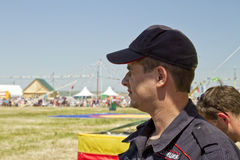 Un policía en una gorra de béisbol mira cuidadosamente en la distancia Foto de archivo