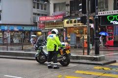 Un policía está haciendo su trabajo en la calle de Hong Kong foto de archivo