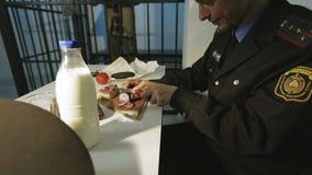 Un policier affamé prépare un dîner de lard, concombre, tomate, lait, pain banque de vidéos