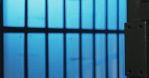 Un poliziotto tiene le manette e chiude la cella di prigione con le chiavi stock footage