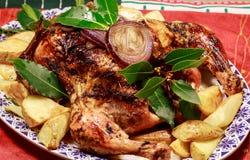 Un pollo arrosto su un letto delle patate al forno fotografia stock