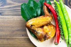 Un pollo asado a la parrilla con la hierba tailandesa fotos de archivo