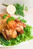 Un pollo entero asó a la parrilla con las verduras frescas y las hierbas archivadas encendido Imagen de archivo