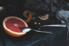 Un pomelo rosado del corte con un cuchillo y una cuchara en una superficie oscura Imagenes de archivo