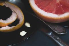 Un pomelo rosado del corte con un cuchillo y una cuchara en una superficie oscura Imagen de archivo