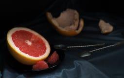 Un pomelo rosado del corte con un cuchillo y una cuchara en una superficie oscura Fotografía de archivo