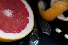 Un pomelo rosado del corte con un cuchillo y una cuchara en una superficie oscura Fotos de archivo