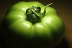 Un pomodoro verde alla luce e ad ombra Immagini Stock