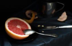 Un pompelmo rosa del taglio con un coltello e un cucchiaio su una superficie scura Immagine Stock