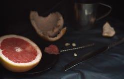 Un pompelmo rosa del taglio con un coltello e un cucchiaio su una superficie scura Fotografie Stock Libere da Diritti
