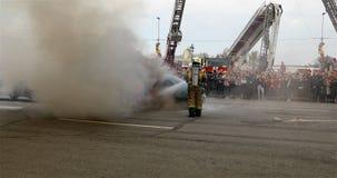 Un pompier avec un réservoir sur le sien de retour met la voiture sur la chaussée clips vidéos