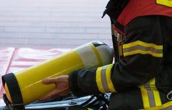 Un pompiere con il cilindro di ossigeno Fotografie Stock