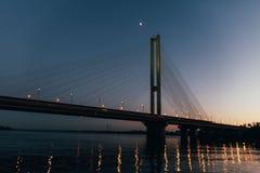 Un pont énorme à l'arrière-plan du coucher du soleil, qui divise la ville en deux parts Photos libres de droits