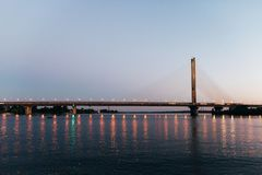 Un pont énorme à l'arrière-plan du coucher du soleil, qui divise la ville en deux parts Image stock