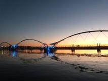 Un pont au-dessus d'un lac calme avec les lumières et les ombres se reflétantes Images libres de droits