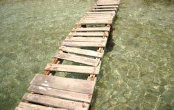 Un pont cassé au-dessus de l'eau cristalline Photographie stock libre de droits