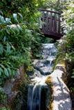 Un pont en bois au-dessus d'une cascade photo stock