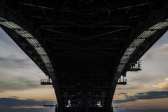 Un pont massif en fer pendant le coucher du soleil Photos stock