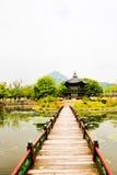 Un pont menant à une pagoda orientale de style Photos stock