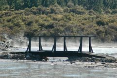 Un ponte di legno sopra uno stagno di cottura a vapore del fango Immagini Stock Libere da Diritti
