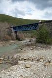 Un ponte ferroviario della montagna sopra acqua in un giorno di esterno della costruzione Fotografia Stock