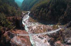 Un ponte sospeso attraverso un fiume della montagna Fotografia Stock Libera da Diritti