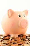 Un porcellino salvadanaio su un mucchio di euro centesimo conia Fotografia Stock Libera da Diritti