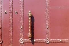 Un a porta chiusa con i modelli sulle strisce La maniglia verticale della porta Immagini Stock Libere da Diritti