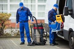 Un portiere Unloading Cleaning Equipment di due maschi dal veicolo immagine stock libera da diritti