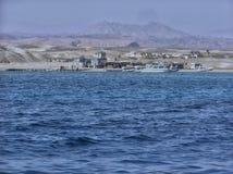 Un porto delle navi attraccate in mare accanto ad un paesino di montagna fotografia stock libera da diritti