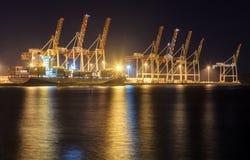 Un porto occupato alla notte Una nave da carico intraprende i contenitori fotografia stock