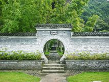 Un portone circolare della luna del cortile di stile cinese conduce ad un giardino interno con i bambù verdi fotografia stock