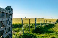Un portone e un recinto di legno attraverso bello terreno coltivabile Fotografia Stock