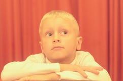 Un portrait d'épaule d'un petit garçon s'asseyant sur une chaise avec un visage réfléchi Photographie stock