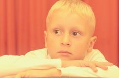 Un portrait d'épaule d'un petit garçon s'asseyant sur une chaise avec un visage réfléchi Photo stock