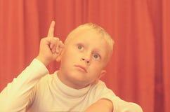 Un portrait d'épaule d'un petit garçon s'asseyant sur une chaise avec un visage réfléchi Image libre de droits