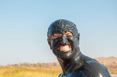 Un portrait d'un homme enduit dans la boue et le sourire photos libres de droits