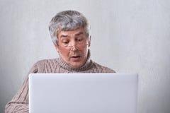 Un portrait d'homme mûr étonné en verres ayant déconcerté l'expresion tout en regardant dans l'écran d'un ordinateur portable Un  Images libres de droits