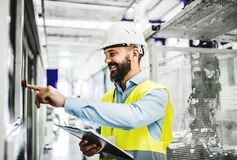 Un portrait d'un ingénieur industriel d'homme avec le presse-papiers dans une usine, fonctionnant image stock